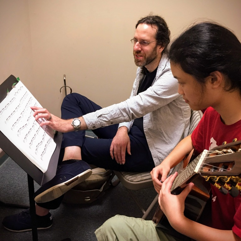 Adam teaching a guitar student